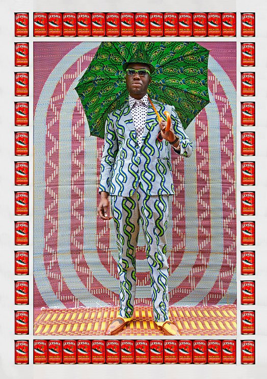 Man standing in African-Print suit holding an umbrella against a background of circles