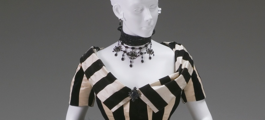 Up close of a short sleeved striped gown. A broach, matching the necklace, sits in the middle of the dress where two folds meet.