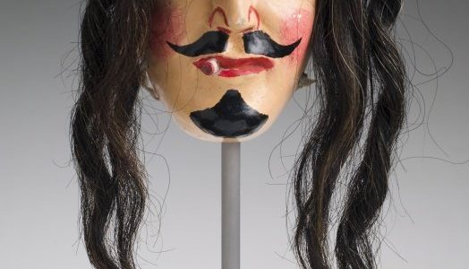 Carved mask from Mexico that resembles a man with long hair and a mustache
