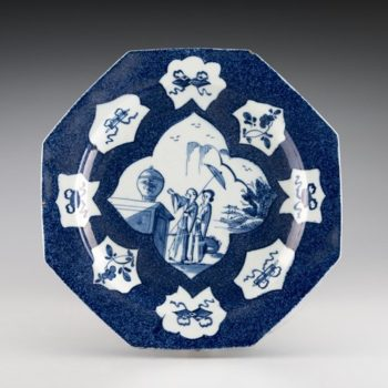 octagonal plate with ribbons and two people painted onto it in the center