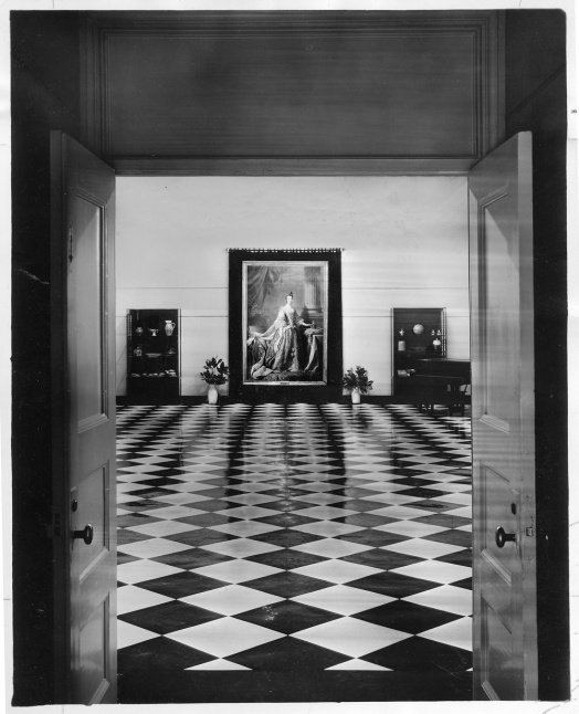 Vintage photograph through a doorway leading into an atrium with a painting of Queen Charlotte hanging on the back wall