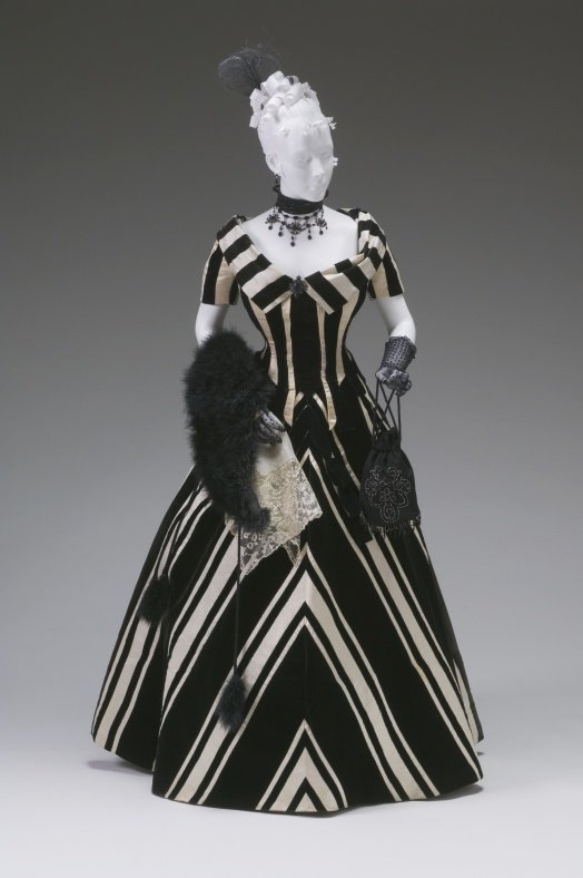Short sleeve, floor length gown with a striped pattern. The mannequin is holding a fur shaw and a small bag.