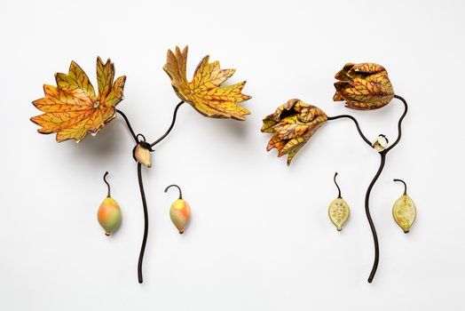 two porcelain twigs with leaves and seed pods attached.