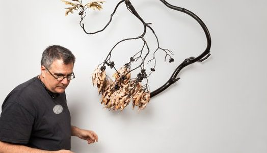 Michael Sherrill with one of his creations. The artwork resembles a branch with leaves hanging off of it