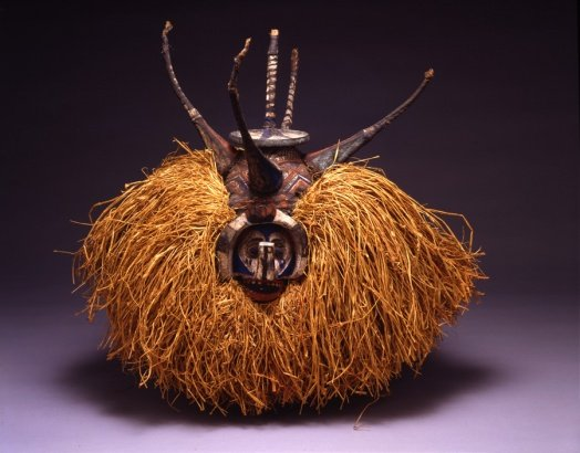 Wooden sculpture of Antelope head with straw-like fringe on either side of the face