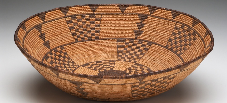 A large bowl with the opening being the widest part. It has triangle and checkered designs on the inside as well as the outside.