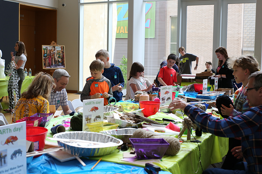 Sunday Funday in the Atrium of Mint Museum Uptown. Children and families sit around a table and create arts and crafts