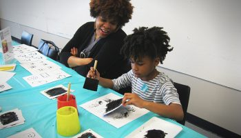 A mom and son sit at a table and make ink print art