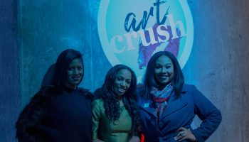 Three women standing in front of the logo for Art Crush, the podcast produced for the Mint Museum