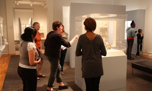 A group of 5 women in a gallery space looking at a set of silver teapots