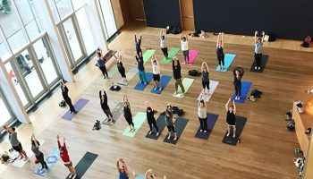 view from above of people in the atrium of mint museum uptown doing yoga.