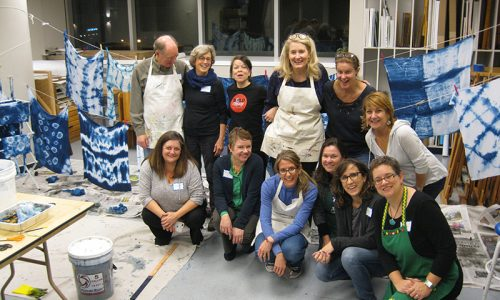 a group who attended an adult art party at mint museum uptown. They stand together posing in front of their shibori tye dye fabrics
