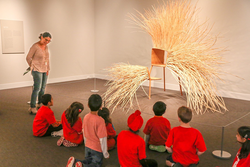 A group of children sit in front of a large wooden chair sculpture and listen to a woman who is standing up and teaching them about it