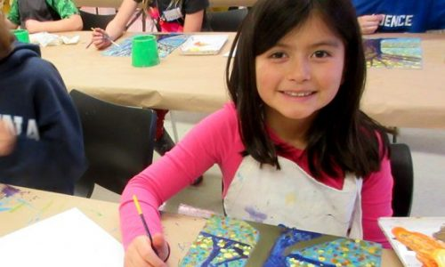A girl sitting at a table smiles as she paints a tree