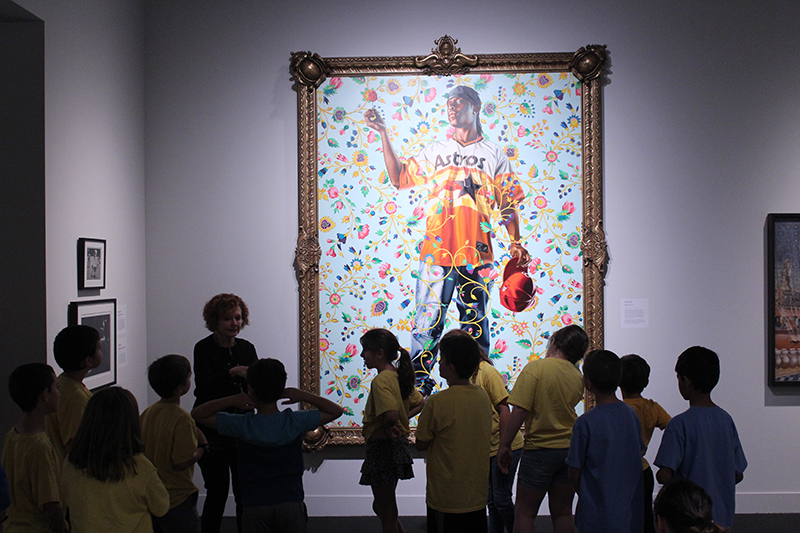 A group of children on a field trip stand in front of a painting in mint museum uptown