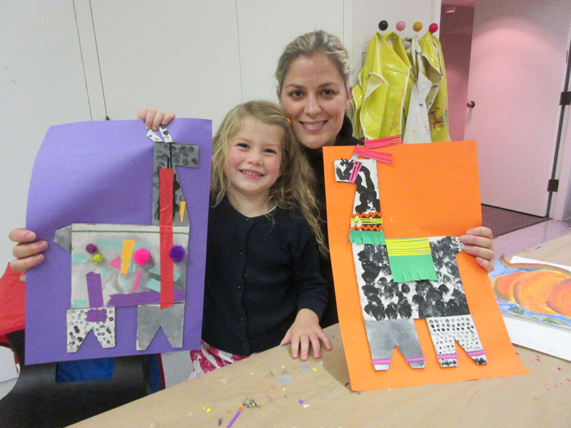 A woman and a child hold up collage art that they made. both collages resemble llamas
