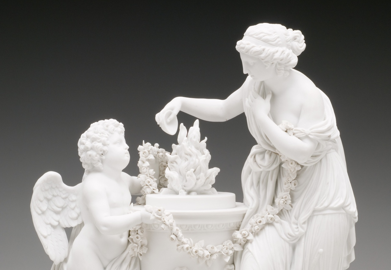 A detailed shot of a state of an angel and a woman standing next to a pedestal