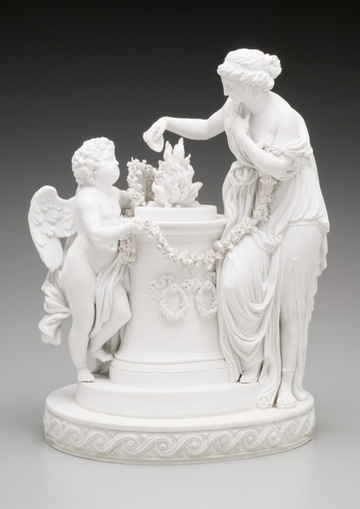 A porcelain statue of an angle and a woman standing next to a pedestal