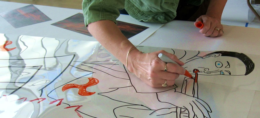 A transparent sheet of plastic being drawn on with markers