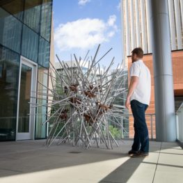 A man standing on the patio space at Mint Museum Uptown looking at a structure made of metal rods.
