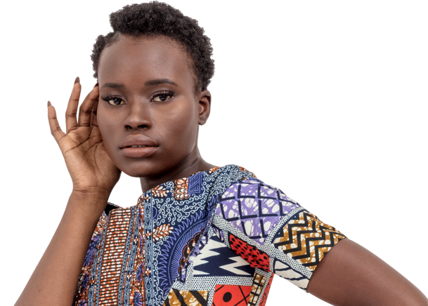 A woman standing facing the camera with her hand on the side of her face. She is wearing traditional African-print