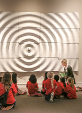 A person kneeling in front of a large piece of artwork at Mint Museum Uptown, speaking to a group of children.