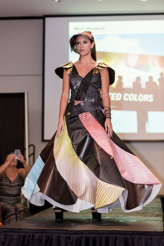 A dress worn by a model walking down a runway. The dress is made out of a heavy plastic material. The model is wearing a matching hat.