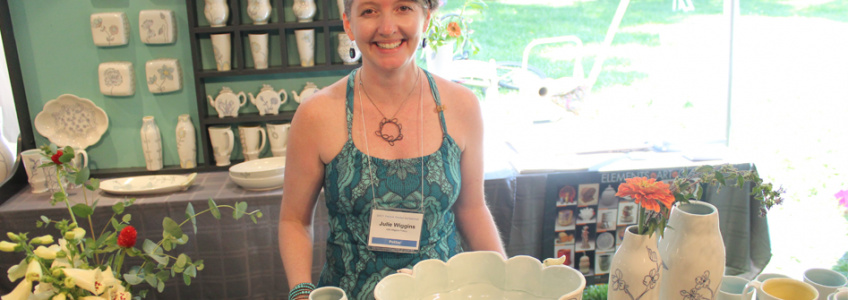 Julie Wiggins standing at the Potters Market Invitational, behind different ceramics decorated with flowers