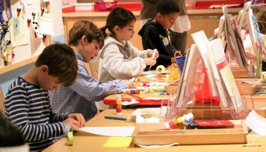 Children sitting at a table using scissors and glue to make crafts.