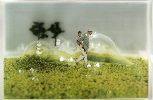 An adult carrying a child on his back through a field of larger-than-life bubbles