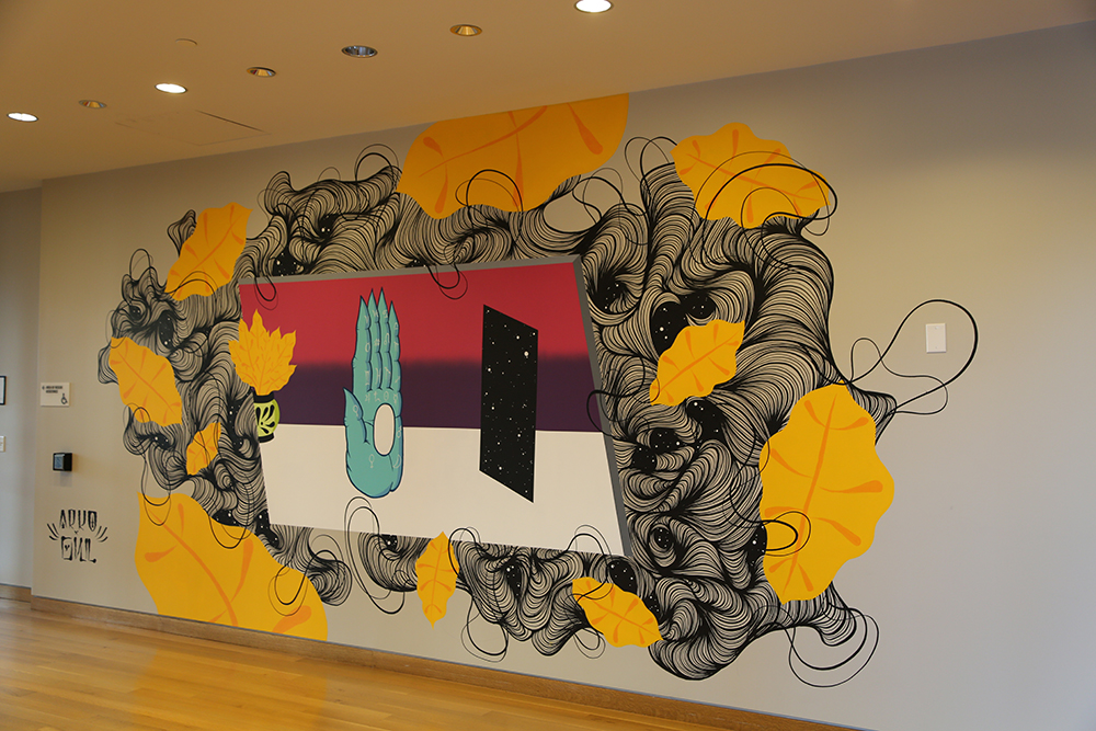 A mural in the entry way of mint museum uptown by ark and owl. Large leaves and curved lines surround a pointy monster-like hand and a square that resembles outer space