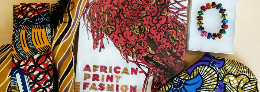 African-Print Fashion Now! exhibition catalog, with a tie, bag, and bracelet from the collection