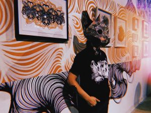 Arko posing in front of a mural they did