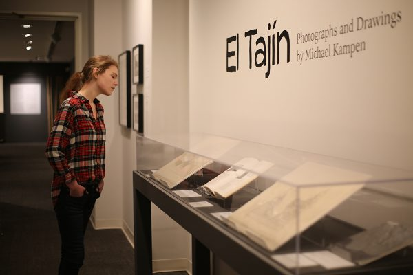 "A woman looks into the glass case holding drawings from the ""El Tajin"" exhibition at mint museum Randolph"