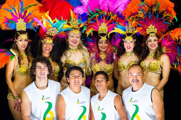 A group of men and women pose for the photo. the men are wearing soccer jerseys and the women are wearing feathery head pieces