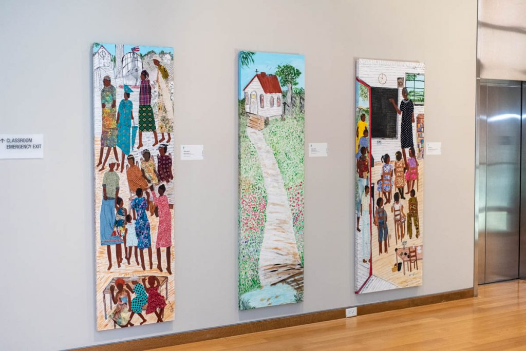three long paintings by nellie ashford, hanging the entry way of mint museum uptown
