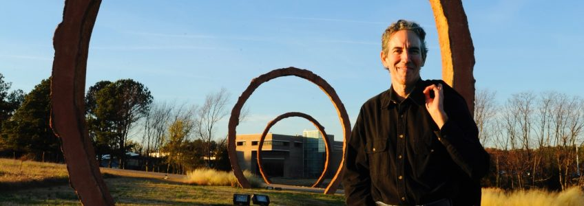 A man standing in front of a sculpture comprised of large ovals protruding from the ground