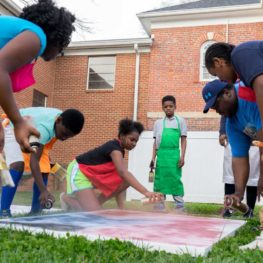 A group of children and adults stand in a grassy area leaning over an art board. they are all holding spray paint cans and using them to decorate the art board.