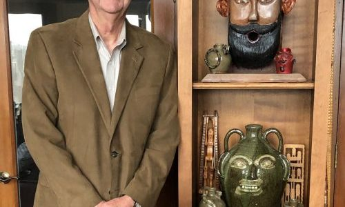 Dr. Allen Huffman and a few objects in his collection of folk art pottery.