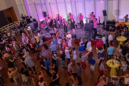 Mint to move at mint museum uptown. the atrium is filled with people dancing along to performers singing on a stage