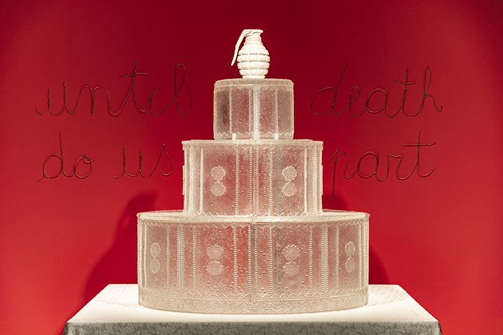 "Wedding cake made of glass with a white grenade used as a topper. the words ""until death do us part"" words on the backdrop"