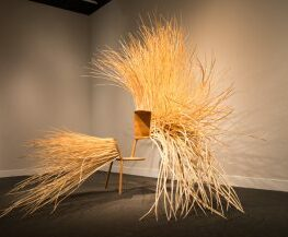 A wooden chair covered in long strips of wooden spikes protruding from the surface of the desk