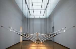 Undulating glass pipes forming repetitive geometric figures. The pipes hang from the ceiling in a large spacious room.