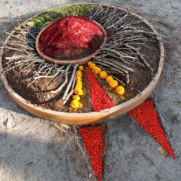 A large circle made of wood filled with colored dirt, sticks, and moss