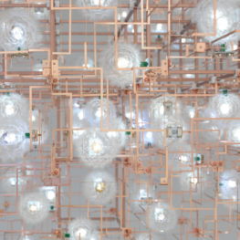 Detailed view of a hanging art installation. Thin copper pipes cross paths to form what resembles the inside of a computer. Dandelions are attached to the copper at various points.