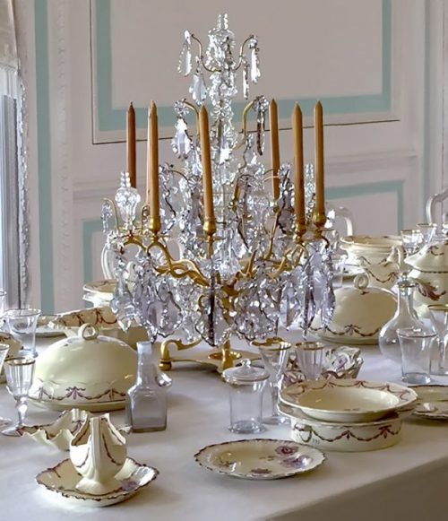 elegantly dressed table with a large crystal candle holder as a centerpiece