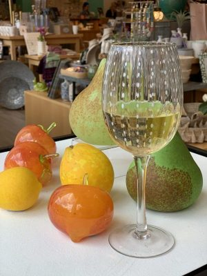 wine glass with wine and glass fruit on a table