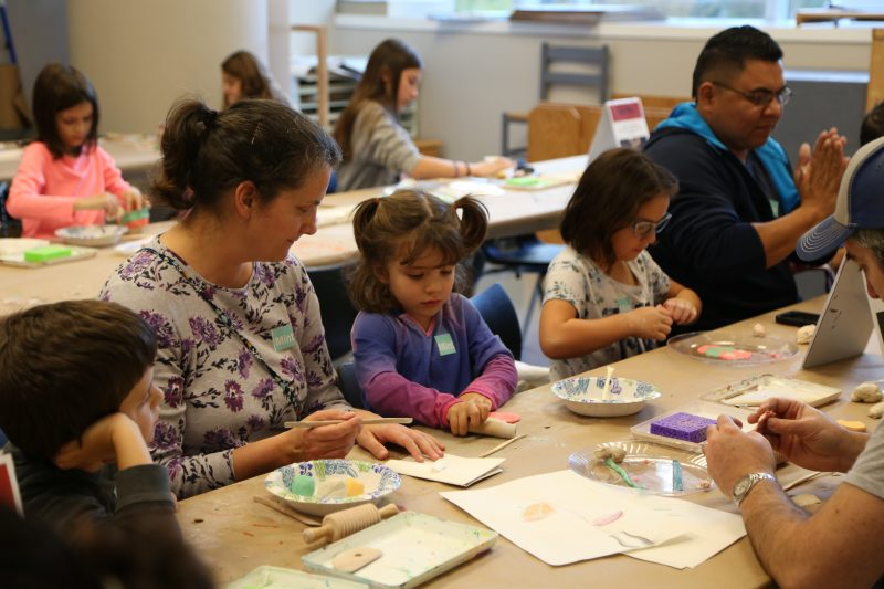 Parents and kids sit around a table and make sculptures out of clay