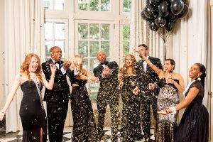 People in tuxedos and formal gowns celebrating together