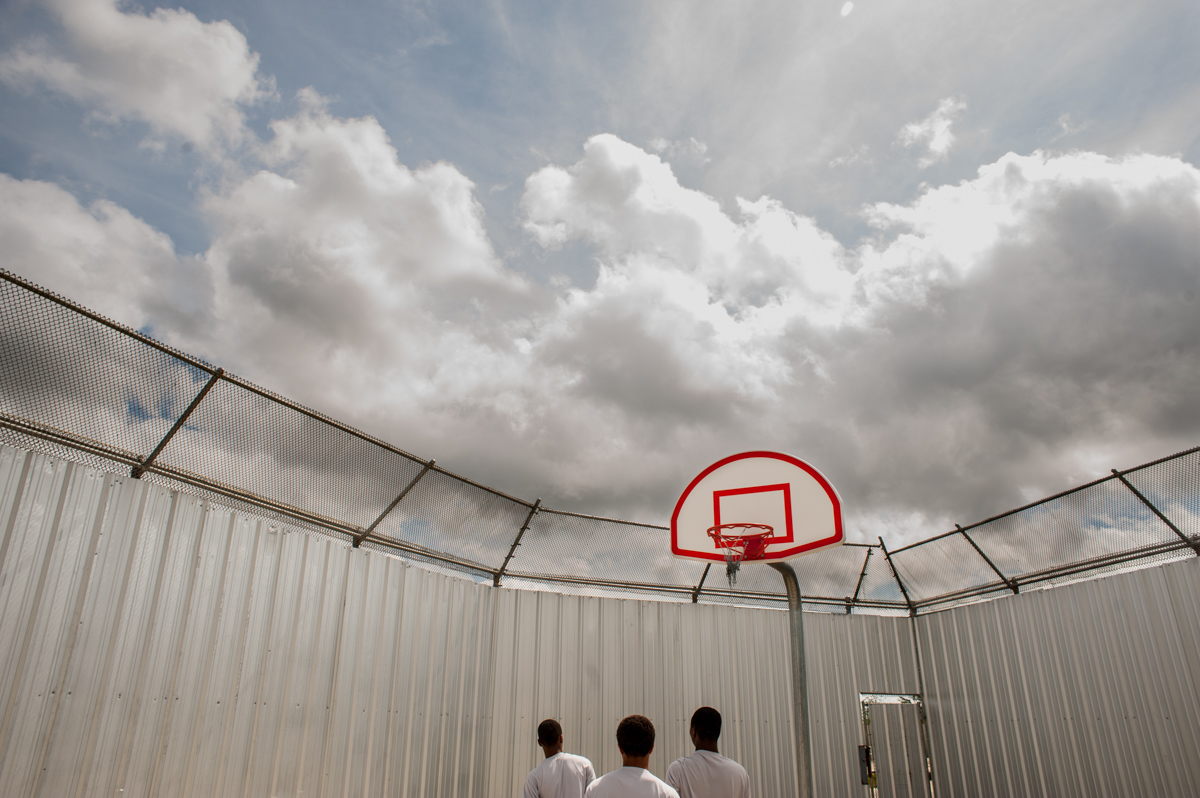 Raymond Thompson, Jr. Teen boys playing basketball at the Youth Study Center juvenile detention facility in New Orleans, Louisiana, 2004. © Raymond Thompson, Jr.